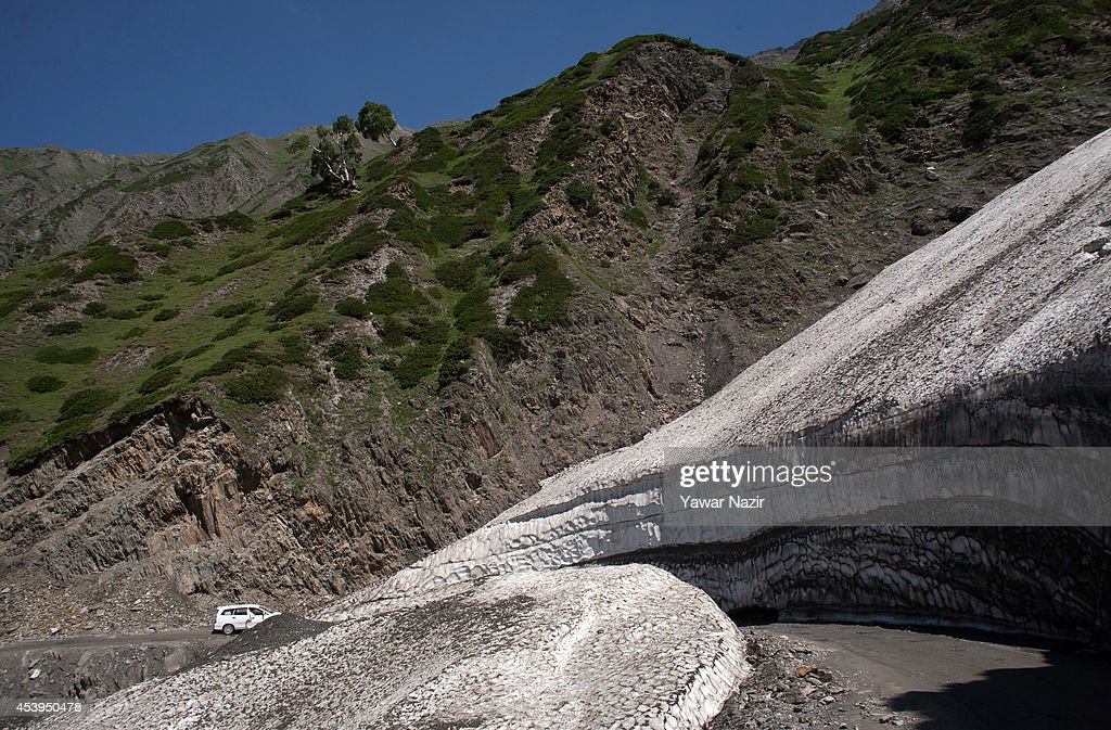 A vehicle passes through the snow-cleared Srinagar-Leh highway along a treacherous pass on August 22, 2014 in Zojila, about 108 km (67 miles) east of Zojila, has an impressive location, enclosed by Kashmir valley on one side and Drass valley on the other side and functions as a major link between Ladakh and Kashmir, is considered to be the World's most dangerous pass is located at 3529 meters. The average snow buildup on the rocky Zojila- which is part of the 443 km (275 miles) long Srinagar-Leh highway- normally stays in the level of 15 to 25 meters and is closed for half year. It opens up in late spring and witnesses violent breezes because of the conical shape. Travellers on the pass have to face and withstand snowstorms, fierce air currents, cold and highly dangerous circumstances.