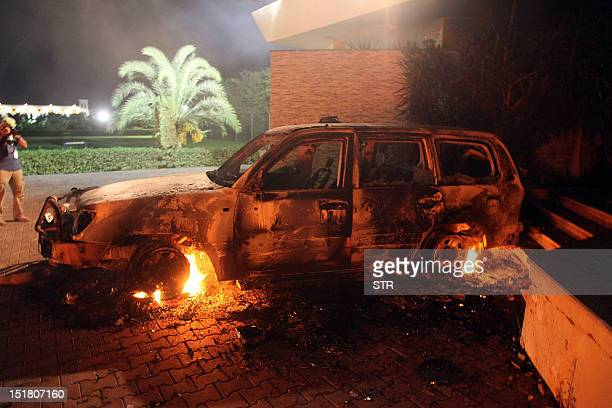 A vehicle sits smoldering in flames after being set on fire inside the US consulate compound in Benghazi late on September 11 2012 An armed mob...