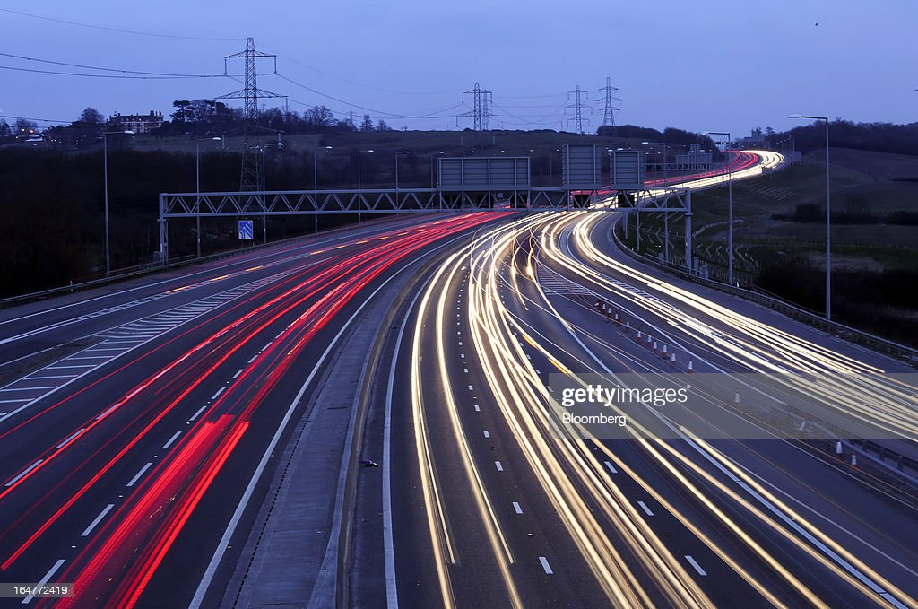 Vehicle tail lights and head lights are seen as they move in both directions along the carriageway near to junction 26 on the northern section of the M25 motorway near London, U.K., on Wednesday, March 27, 2013. The U.K. government will increase spending on infrastructure projects, including road construction, by an annual 3 billion pounds ($4.6 billion) from 2015 as Chancellor George Osborne seeks to boost economic growth. Photographer: Chris Ratcliffe/Bloomberg via Getty Images