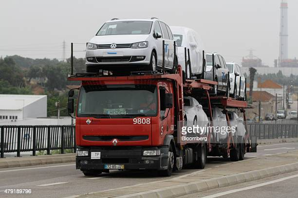 A vehicle transporter carries Volkswagen AG Sharan automobiles as it arrives at the Autoeuropa rollon/rolloff terminal in the Port of Setubal...