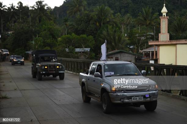 A vehicle transporting the corpses of dead civilians retrieved near the frontline drives over a bridge along with military vehicles providing...