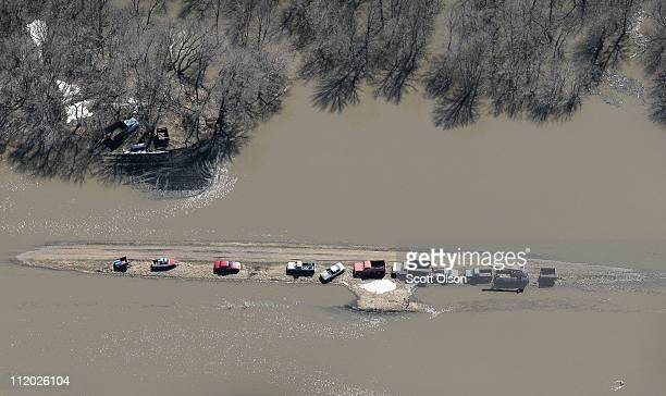 Vehicles and farm equipment are stranded on a flooded stretch of road April 11 2011 near Fargo North Dakota Although the Red River crested in Fargo...