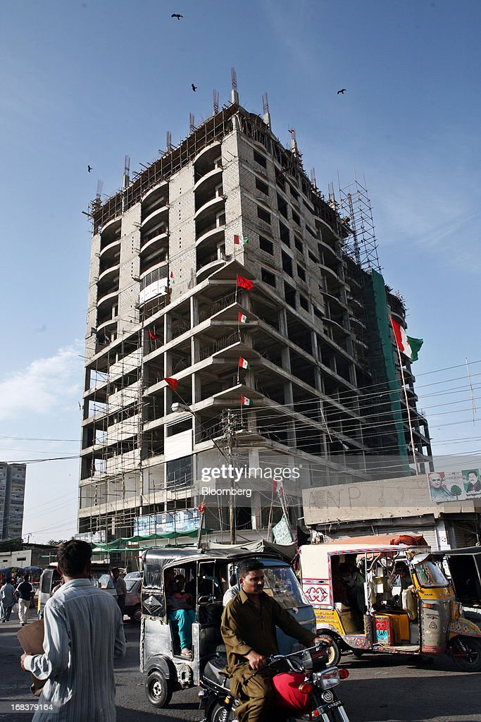 Vehicles and pedestrians pass a building under construction in Karachi, Pakistan, on Wednesday, May 8, 2013. Pakistan is to hold parliamentary elections on May 11. According to opinion polls, Nawaz Sharif of the Pakistan Muslim League-N (PMLN) leads Imran Khan of Pakistan Tehrik-e-Insaf (PTI) in the race to replace president Asif Ali Zadari and become Pakistan's 12th president. Photographer: Asim Hafeez/Bloomberg via Getty Images