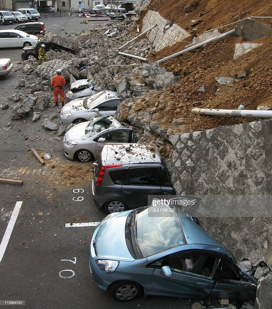 Vehicles are crushed by a collapsed wall at a carpark in Mito city in Ibaraki prefecture on March 11 2011 after a massive earthquake rocked Japan...