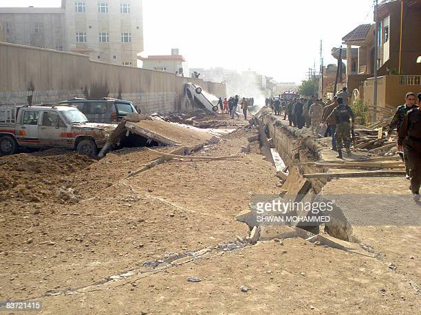 Vehicles are damaged and flipped over as people gather at the scene of a gas pipe explosion along a street in the northern Kurdish city of...