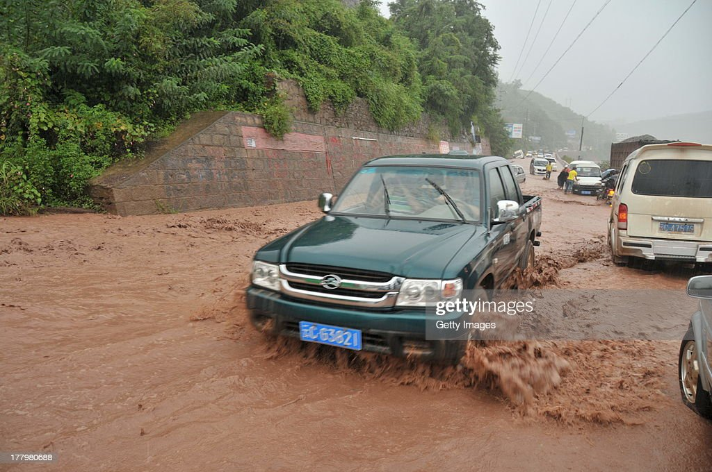 Vehicles are driven along a landslide-hit road on August 25, 2013 in Yiliang, China. Rainstorm-triggered landslides hit the Yiliang county of Yunnan province in this weekend, causing several road closures.