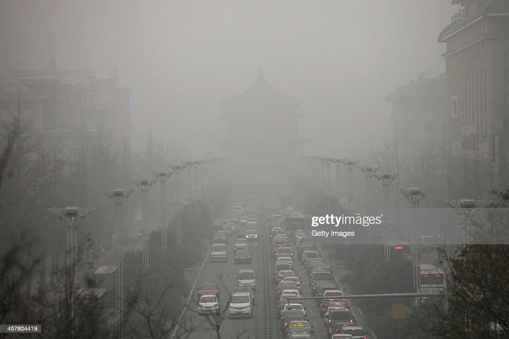 Vehicles are driven along a road as heavy smog engulfs the city on December 18, 2013 in Xi An, China. Heavy smog has shrouded Xi'an for two days, and local environment agency advised people to stay indoors.
