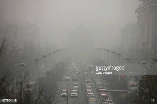 Vehicles are driven along a road as heavy smog engulfs the city on December 18 2013 in Xi An China Heavy smog has shrouded Xi'an for two days and...
