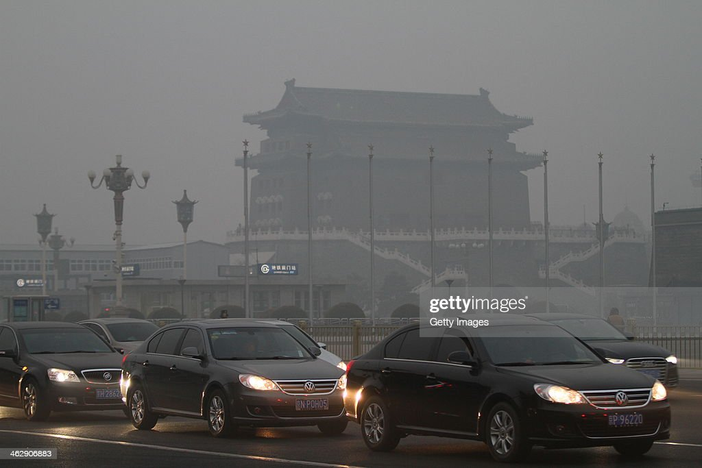 Vehicles are driven along a road on January 16, 2014 in Beijing, China. Beijing Municipal Government issued a yellow smog alert this morning.
