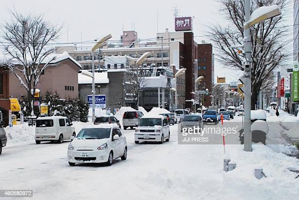 Vehicles are seen on a snowcovered street in Obihiro in Japan's northern island of Hokkaido on December 17 2014 Northern Japan was in the grip of a...