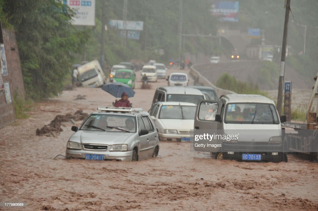 Vehicles are trapped on a landslide-hit road on August 25, 2013 in Yiliang, China. Rainstorm-triggered landslides hit the Yiliang county of Yunnan province in this weekend, causing several road closures.
