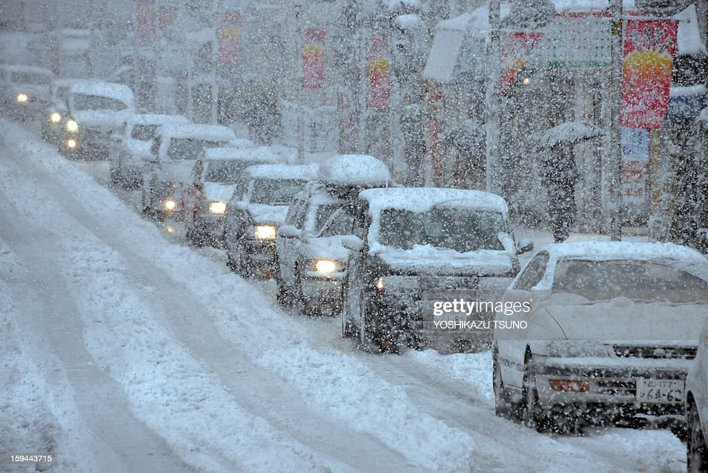 Vehicles come to a standstill on a snow and ice covered road in Tokyo on January 14, 2013. A storm system grasped central Japan on January 14, causing heavy snow fall around the Japanese capital. AFP PHOTO / Yoshikazu TSUNO