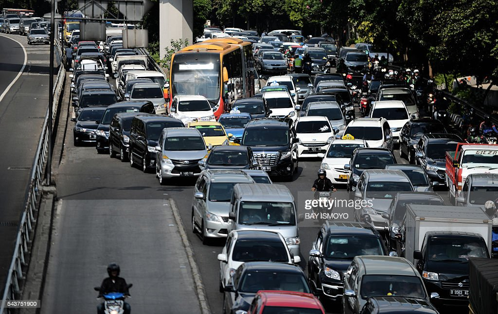 Vehicles commute on a road during afternoon rush hour in Jakarta on June 30, 2016. Indonesia launched a tax amnesty in a bid to give Southeast Asias top economy a multibillion-dollar boost, defying criticism the move will let evaders off the hook. / AFP / BAY