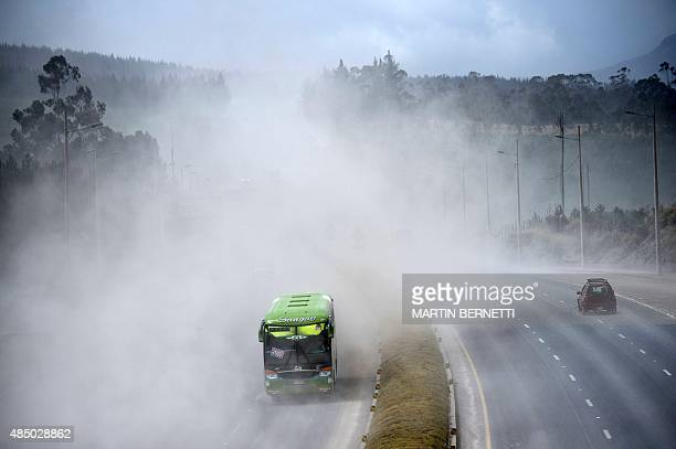 Vehicles drive along a road covered by ashes of the Cotopaxi volcano in Lasso Ecuador on August 23 2015 A dozen towns of central Ecuador including...
