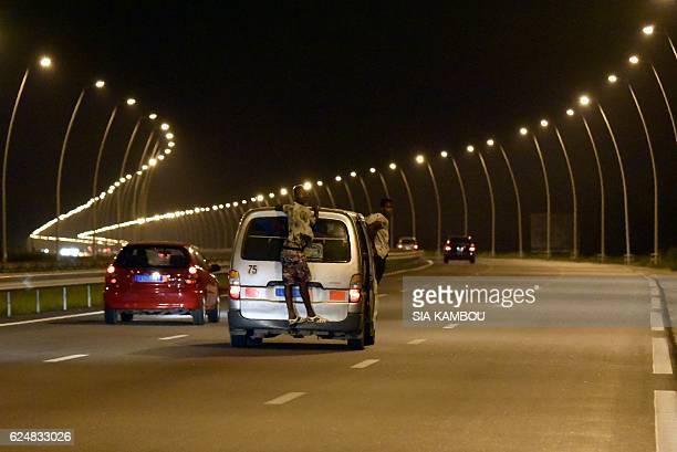 TOPSHOT Vehicles drive along the highway between Abidjan and GrandBassam on November 20 2016 / AFP / Sia KAMBOU