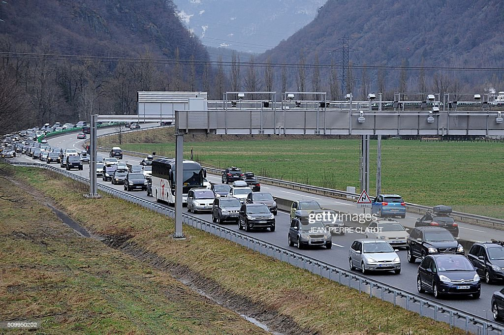 Vehicles drive at reduced speed on February 13, 2016 on RN 90 road near Cevins in the French Alps, during a crossover of people going to or coming from the ski stations during the school holidays. CLATOT