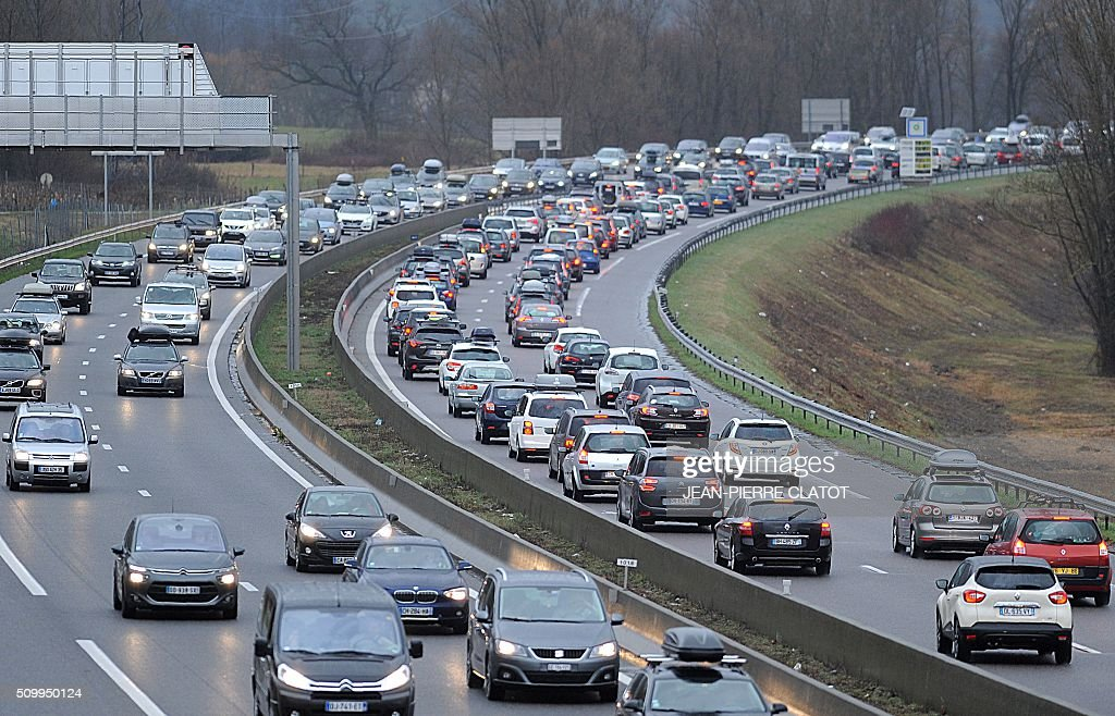 Vehicles drive at reduced speed on February 13, 2016 on the A 43 road near Chignin in the French Alps, during a crossover of people going to or coming from the ski stations during the school holidays. CLATOT