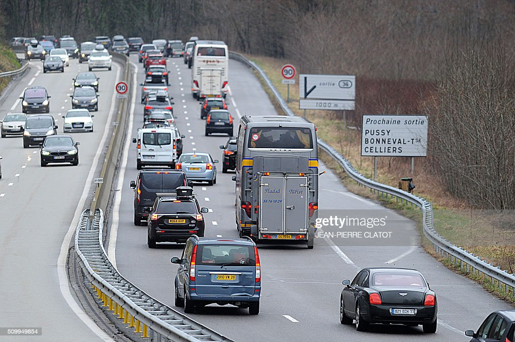 Vehicles drive at reduced speed on February 13, 2016 on the RN90 near Cevins, in the Tarentaise valley in the French Alps, during a crossover of people going to or coming from the ski stations during the school holidays. CLATOT