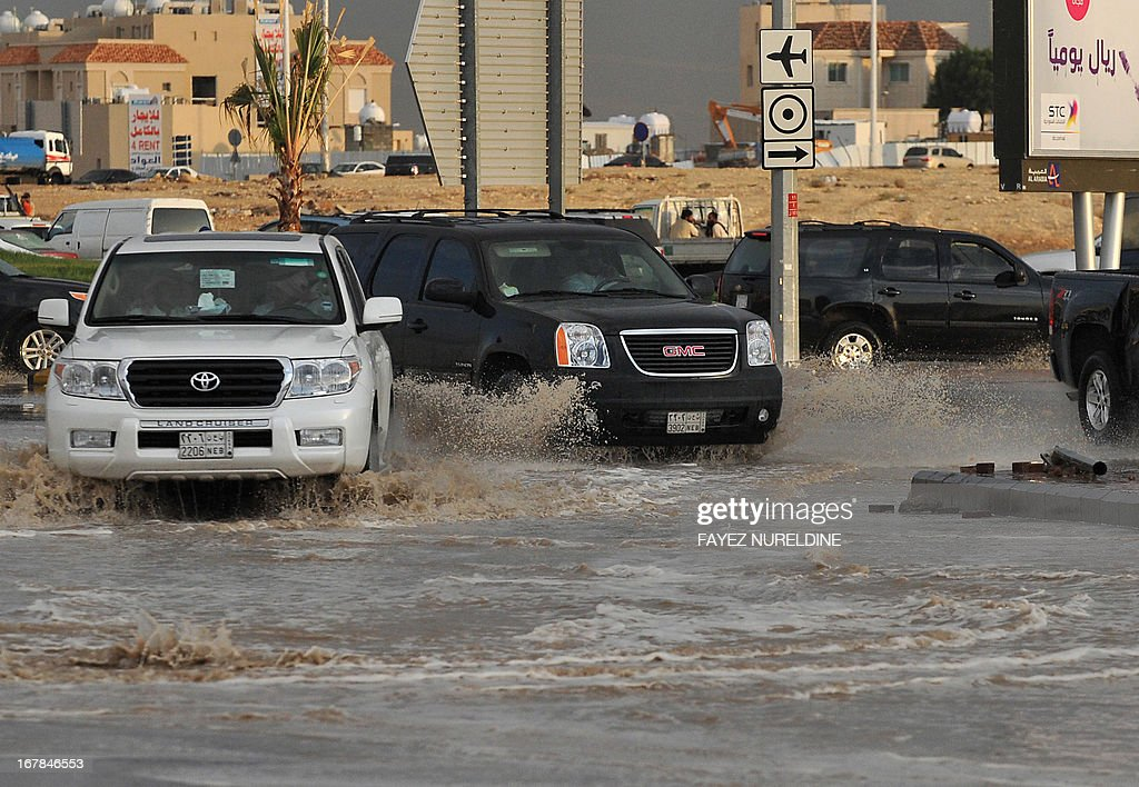 Vehicles drive on a flooded street on May 1, 2013, in the north of the Saudi capital Riyadh. Sixteen people have died and three more are missing in Saudi Arabia after downpours caused flash floods in several areas of the desert kingdom, the civil defence authorities said.