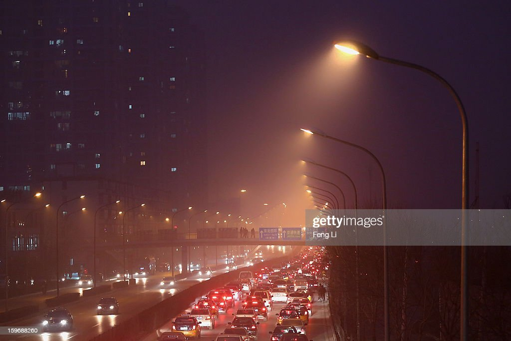 Vehicles drive on the street during severe pollution on January 18, 2013 in Beijing, China.