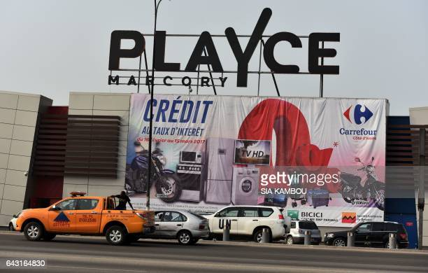 Vehicles drive past a Carrefour supermarket free credit advert in front of the Playce mall in the Marcory district of Abidjan on February 20 2017 /...