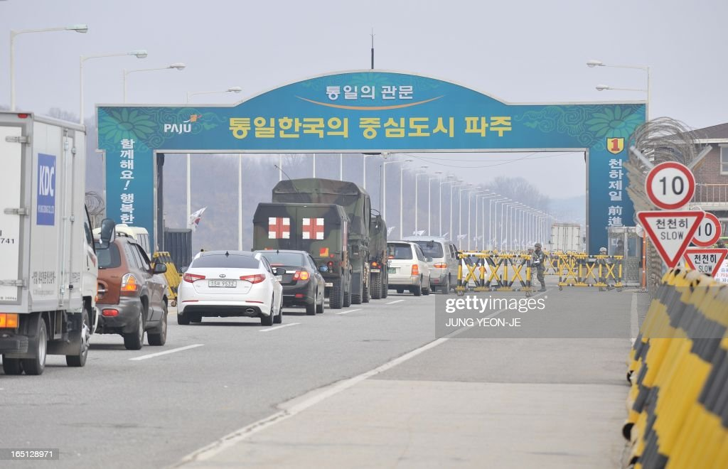 Vehicles drive past a military check point on the road linked to North Korea in Paju near the Demilitarized Zone (DMZ) on April 1, 2013. South Korean workers and cargo on April 1 headed for the Kaesong Industrial Complex without a hitch despite North Korea's recent threat to close the joint industrial zone in the communist country.
