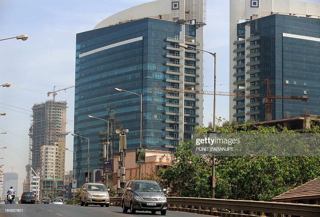 Vehicles drive past newly constructed commercial buildings in Mumbai on March 19, 2013. India's central bank cut its main interest rate by 25 basis points on March 19, its second such reduction this year in an effort to jumpstart the slowing economy. AFP PHOTO/PUNIT PARANJPE
