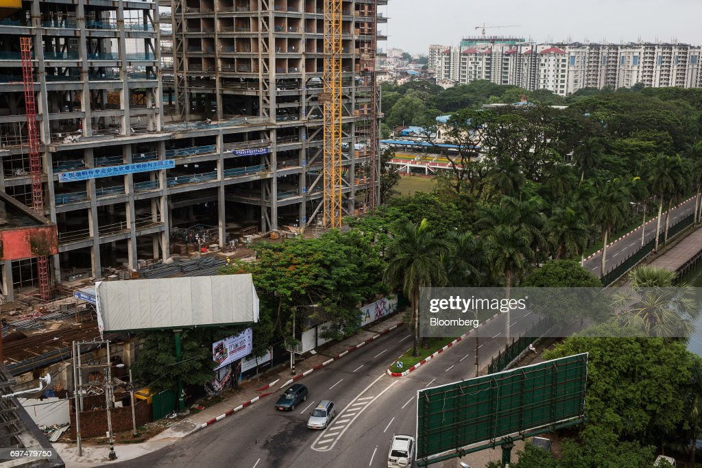 Vehicles drive past the construction site for the Kantharyar Center, a mixed-use development that will also that will also house the Wyndham Grand Yangon Royal Lake hotel, in Yangon, Myanmar, on Monday, June 12, 2017. When the country opened to the outside world in 2011 after decades of military rule, the former British colony held promise as one of the worlds hottest tourist destinations, a last frontier for adventure travel.But it hasn't worked out that way. A construction glut has flooded Myanmar with unused hotel rooms, and poorly regulated building has damaged national treasures like the archaeological site of Bagan. Photographer: Taylor Weidman/Bloomberg via Getty Images