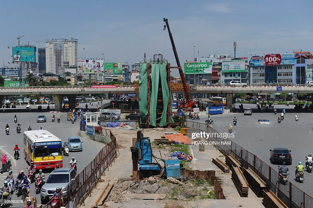 Vehicles drive past the under-construction metro line (C, foreground) in Hanoi on May 31, 2016. Originally scheduled to be completed in 2016, Hanoi's first metro line is now expected to be finished in 2018. / AFP / HOANG