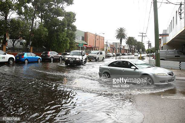 Vehicles drive through a flooded intersection in the suburb of Marrickville on March 15 2016 in Sydney Australia Sydney had been without rain in...
