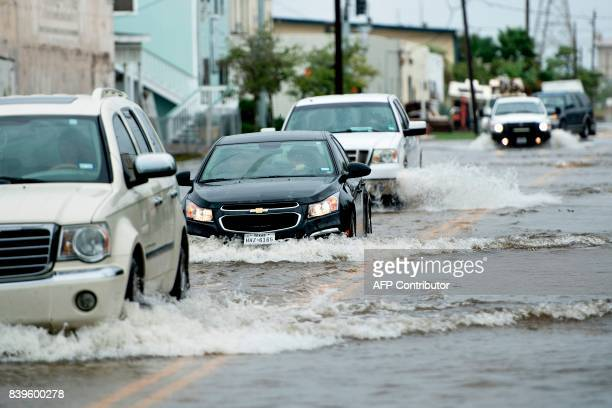 Vehicles drive through a flooded street as the effects of Hurricane Harvey are seen August 26 2017 in Galveston Texas Hurricane Harvey left a trail...