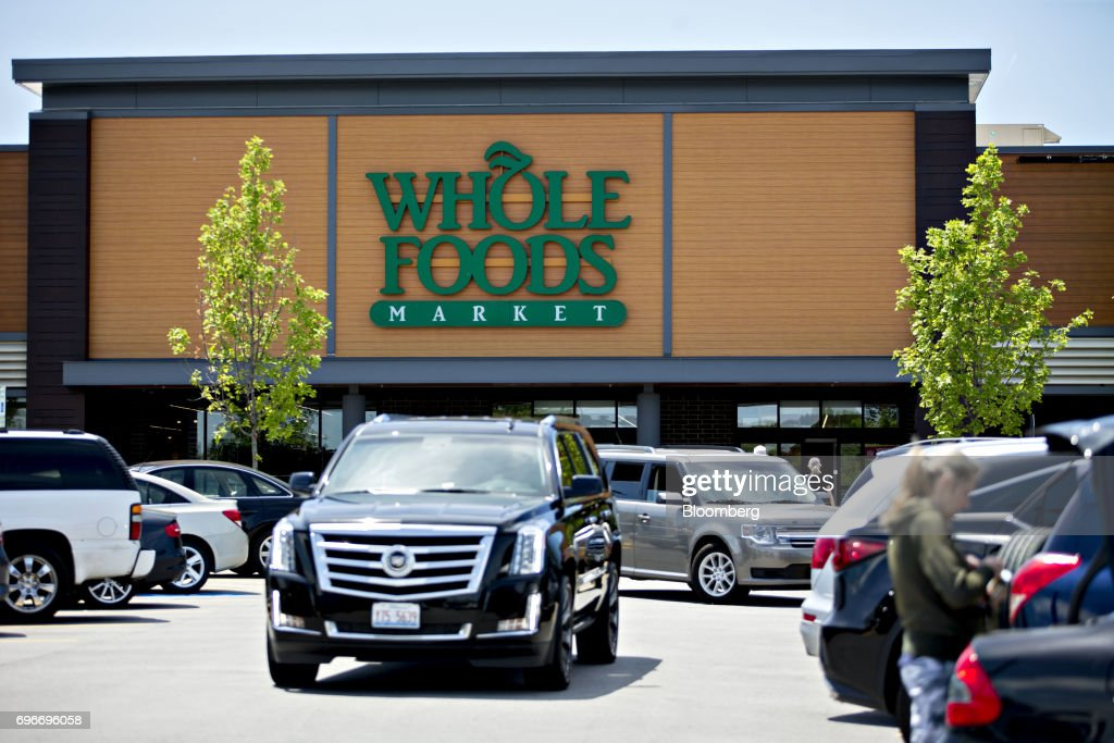 Vehicles drive through the parking lot outside a Whole Foods Market Inc. location in Willowbrook, Illinois, U.S., on Friday, June 16, 2017. Amazon.com Inc. will acquire Whole Foods Market Inc. for $13.7 billion, a bombshell of a deal that catapults the e-commerce giant into hundreds of physical stores and fulfills a long-held goal of selling more groceries. Photographer: Daniel Acker/Bloomberg via Getty Images