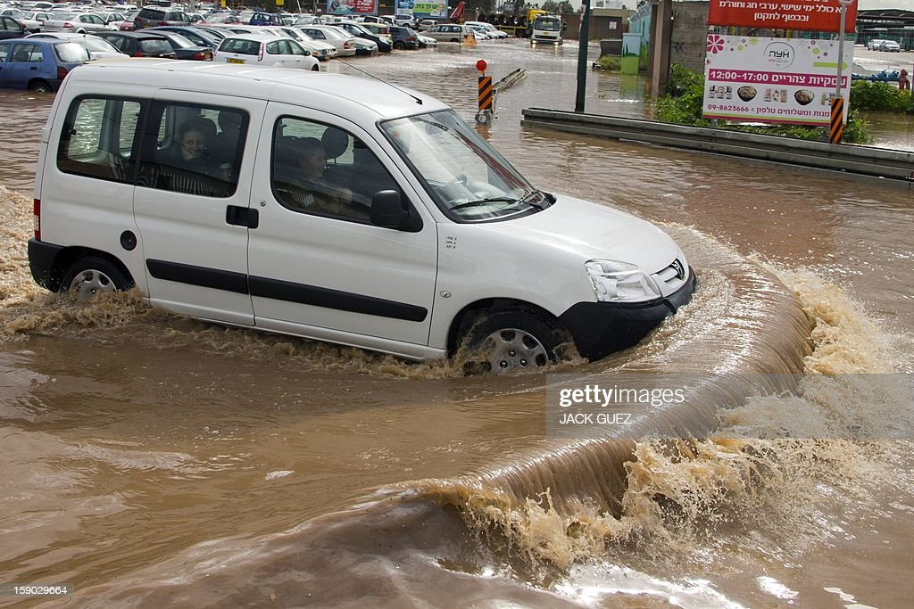 A vehicles drives in flood waters in the Meditrranean coastal city of Netanya, north of Tel Aviv on January 6, 2013. Adverse weather continued in Israel, after an unusually blustery weekend. There were considerable delays on rail lines on the coast, with train travel disrupted between Haifa and Tel Aviv in both directions.