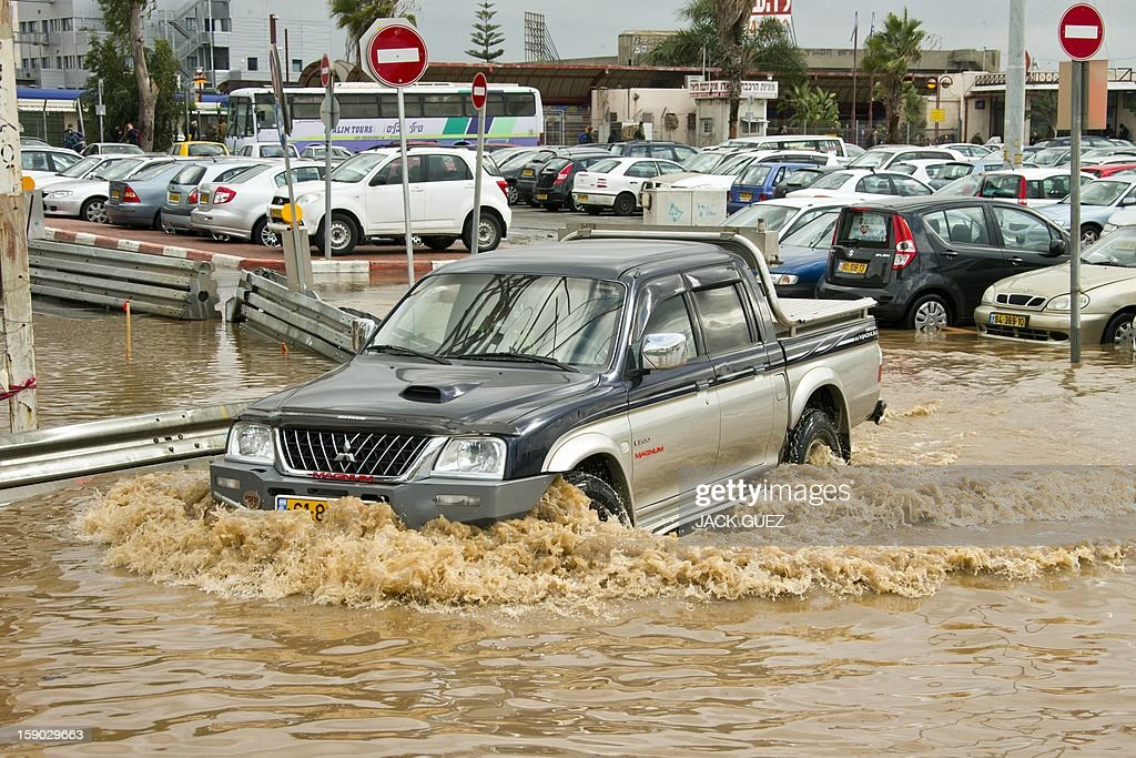 A vehicles drives through flood waters in the Meditrranean coastal city of Netanya, north of Tel Aviv on January 6, 2013. Adverse weather continued in Israel, after an unusually blustery weekend. There were considerable delays on rail lines on the coast, with train travel disrupted between Haifa and Tel Aviv in both directions.