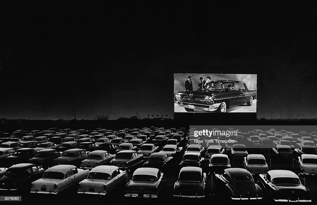 Vehicles fill a drive-in theater while people on the screen stand near a new car, 1950s.