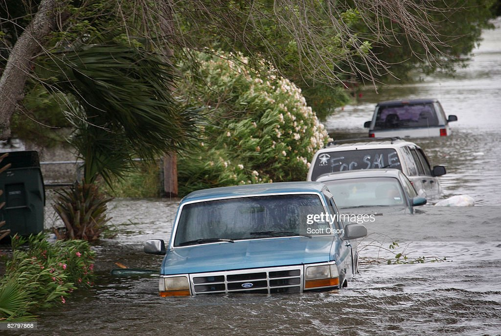 Vehicles flooded by the tidal surge from Hurricane Ike sit along a street September 12 2008 in Galveston Texas The eye of the hurricane is expected...