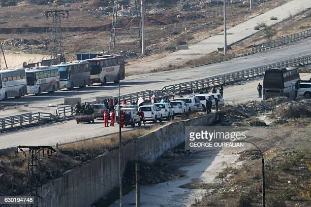 Vehicles from the International Red Cross and from the Syrian Red Crescent wait at the governmentcontrolled crossing of Ramoussa on the southern...