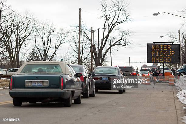 Vehicles line up on Martin Luther King Blvd to receive free cases of water distributed by the National Guard on January 23 2016 in Flint Michigan...