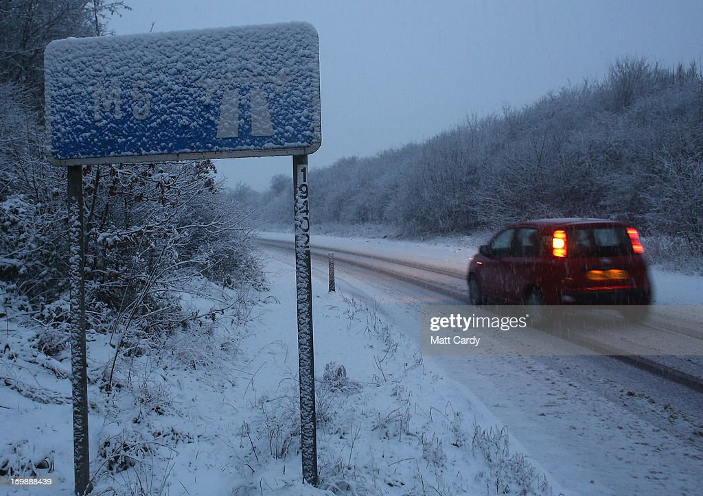 Vehicles make their way around Junction 26 of the M4 motorway as snow falls on January 22, 2013 near Wellington, England. Fresh snow has brought fresh disruption to parts of the UK.