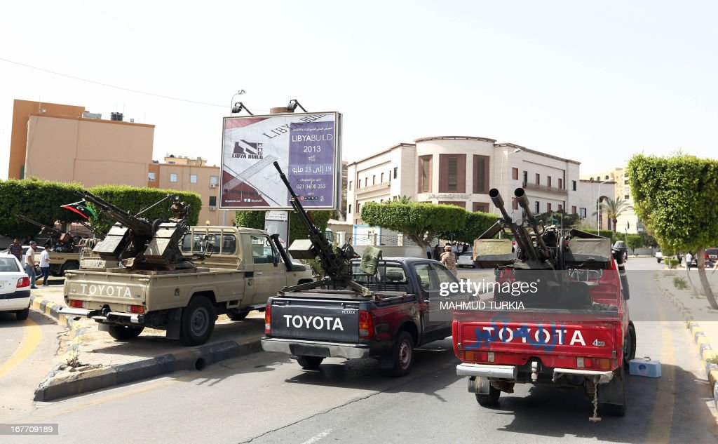 Vehicles, mounted with anti-aircraft guns are parked outside the foreign ministry that has been surrounded by gunmen demanding it be 'cleansed of agents' and ambassadors of ousted dictator Moamer Kadhafi on April 28, 2013 in the Libyan capital Tripoli. The group prevented staff from entering the building said a ministry official who spoke to AFP. The General National Congress, Libya's highest political authority, is studying proposals for a law to exclude former Kadhafi regime officials from top government and political posts.