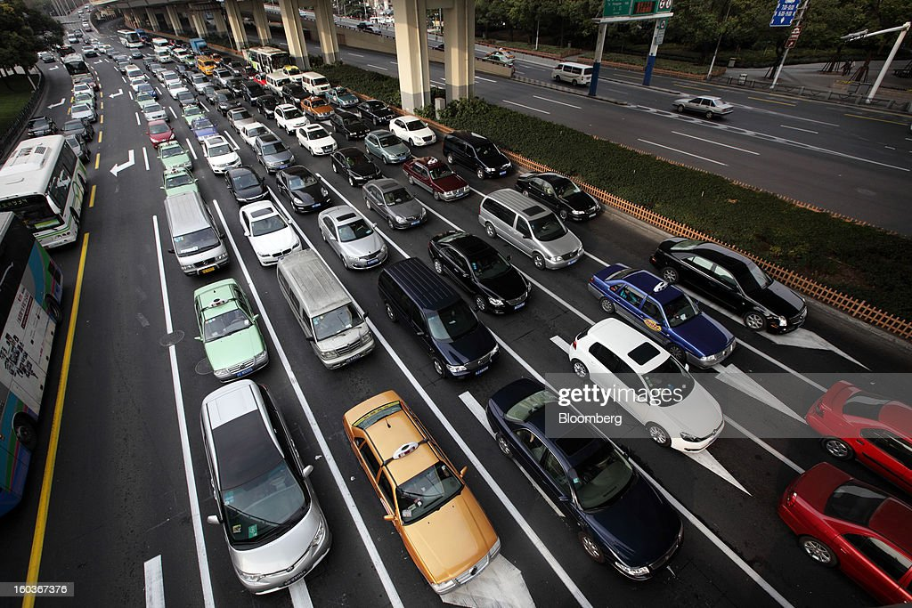 Vehicles move along a road in Shanghai, China, on Tuesday, Jan. 29, 2013. China's economic growth accelerated for the first time in two years as government efforts to revive demand drove a rebound in industrial output, retail sales and the housing market. Photographer: Tomohiro Ohsumi/Bloomberg via Getty Images