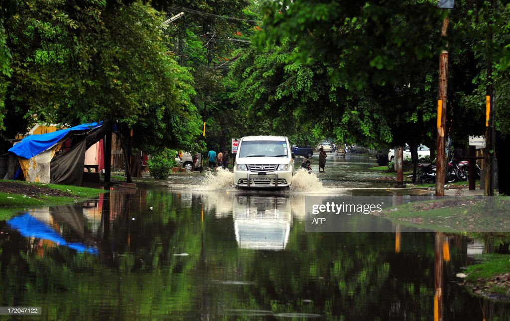Vehicles move along a waterlogged road after heavy rain in Allahabad on July 1, 2013. Construction along river banks will be banned in the devastated north Indian state of Uttarakhand amid concerns unchecked development fuelled June's flash floods and landslides that killed thousands, the state's top official said July 1.