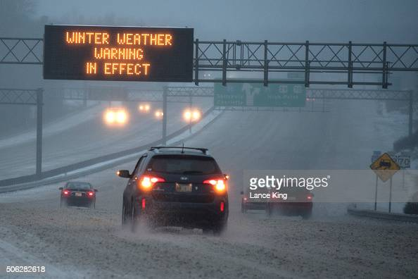 Vehicles move along Interstate 85 as an overhead sign indicates 'WINTER WEATHER WARNING IN EFFECT' during a winter storm on January 22 2016 in...