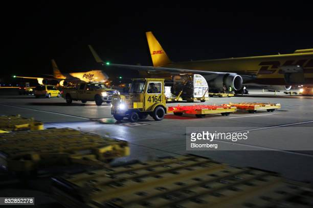 Vehicles move past DHL Worldwide Express cargo jets at the company's hub of Cincinnati/Northern Kentucky International Airport in Hebron Kentucky US...