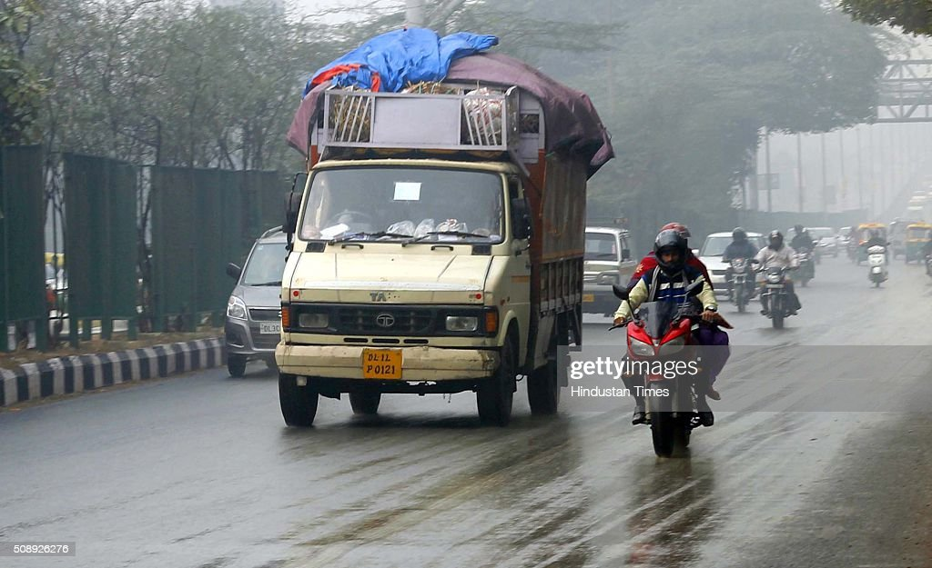 Vehicles moving during a rainy weather at Rajpath on February 7, 2016 in New Delhi, India. Delhiites woke up to an overcast sky accompanied by a drizzle today even as the minimum temperature settled at 13.4 degrees Celsius, four notches above normal.