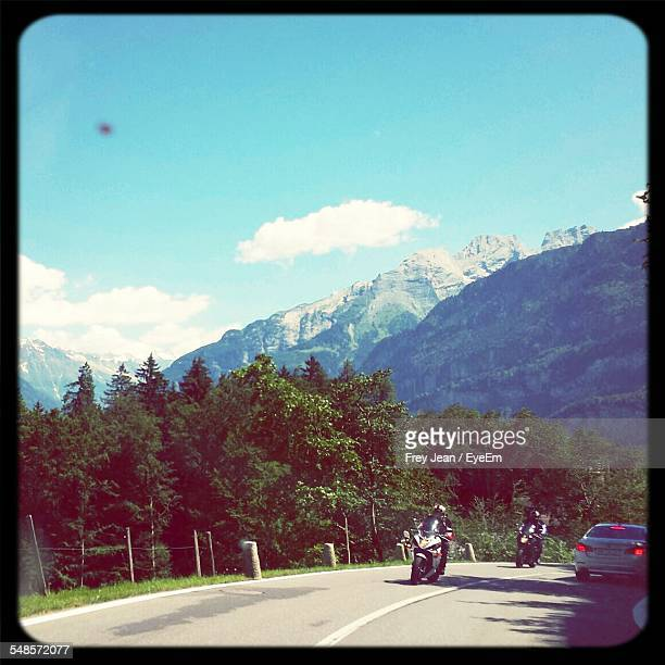 Vehicles On Road In Front Of Mountains Against Sky