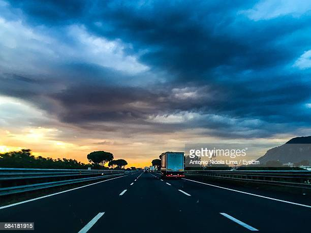 Vehicles On Street Against Cloudy Sky During Sunset