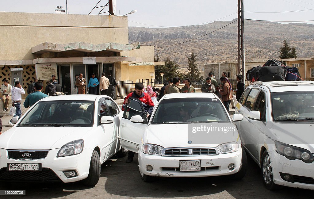 Vehicles park waiting for Syrian families on March 3, 2013 in the Syrian city of al-Jdeideh after they crossed the Lebanese-Syrian border in al-Masnaa on their way back to Syria.