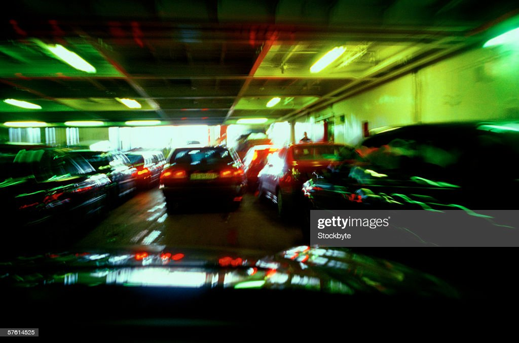 Vehicles parked in a basement parking lot (toned and blurred) : Stock Photo