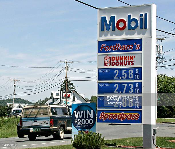 Vehicles pass a display of gas prices at an Exxon Mobil gas station in Lyndonville Vermont US on Wednesday June 17 2009 Gasoline futures fell the...